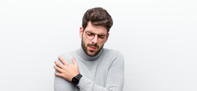Jonge manager man angstig, ziek, ziek en ongelukkig, lijden aan een pijnlijke buikpijn of griep over witte muur