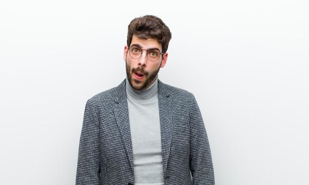 Jonge manager man gevoel verbaasd en verward, met een stomme, verbijsterde uitdrukking op zoek naar iets onverwachts tegen de witte muur