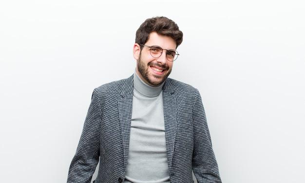 Jonge manager man met een grote, vriendelijke, zorgeloze glimlach, op zoek naar positief, ontspannen en gelukkig, huiveringwekkende witte muur