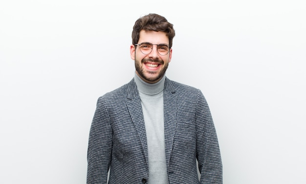 Jonge manager man op zoek gelukkig en mal met een brede, leuke, gekke glimlach en ogen wijd open witte muur