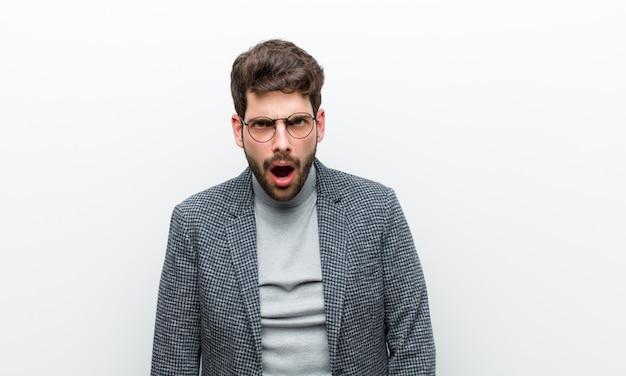 Jonge manager man op zoek geschokt, boos, geërgerd of teleurgesteld, open mond en woedend