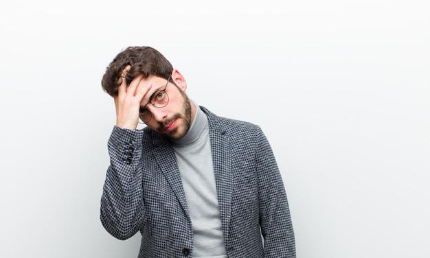 Jonge manager man verveeld, gefrustreerd en slaperig na een vermoeiende, saaie en vervelende taak, gezicht met hand vasthouden