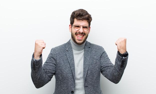 Jonge manager man viert een ongelooflijk succes als een winnaar, ziet er opgewonden en gelukkig uit zeg neem dat! tegen wit