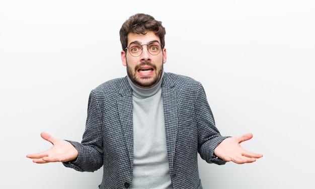 Jonge manager man voelt zich extreem geschokt en verrast, angstig en in paniek, met een gestresste en geschrokken witte muur