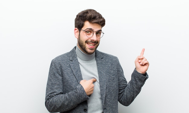 Jonge manager man voelt zich trots en verrast, wijzend op zelfverzekerd, gevoel als succesvol nummer één tegen wit