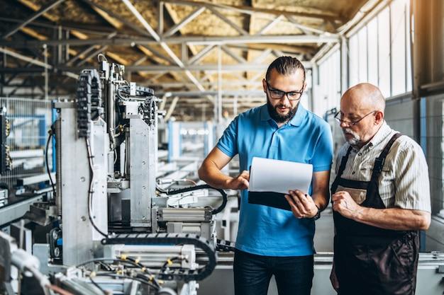 Jonge manager met baard die en werkend proces van volwassen professionele arbeider op de grote fabriek tonen inspecteren.