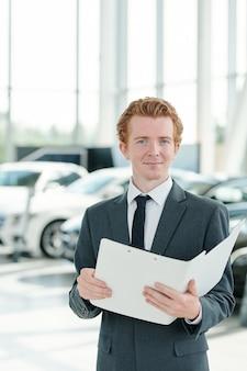 Jonge manager van hedendaags autocentrum met open map met documenten en kwaliteitscertificaten