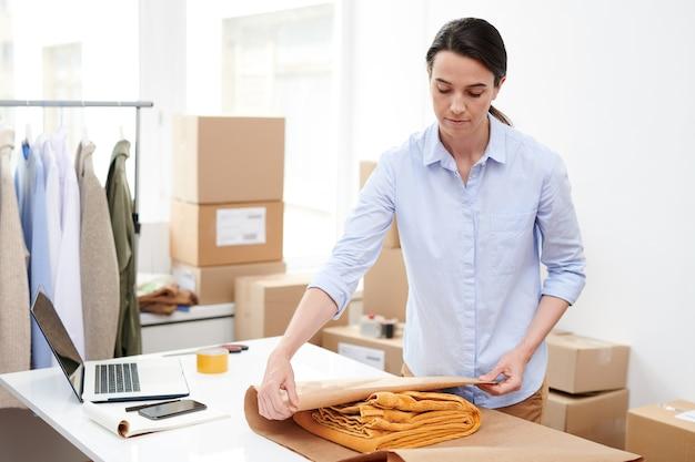 Jonge manager van online winkel die gevouwen gele broek in papier verpakt tijdens het inpakken voordat deze naar de klant wordt verzonden