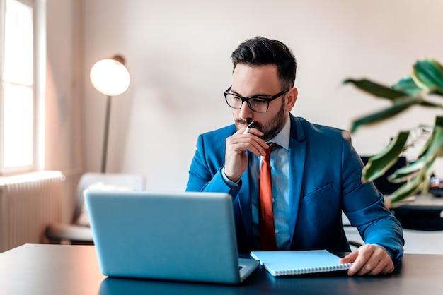 Jonge manager zit aan bureau in heldere office, die op laptop werkt.