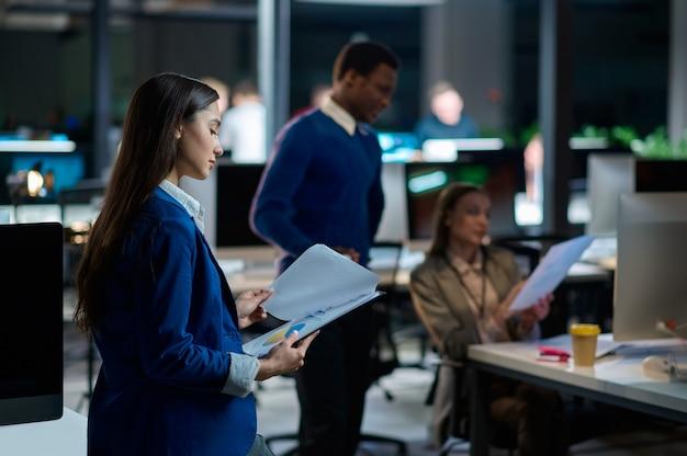 Jonge managers werken in het nachtkantoor. glimlachende mannelijke en vrouwelijke werknemers, donker zakencentruminterieur, moderne werkplek