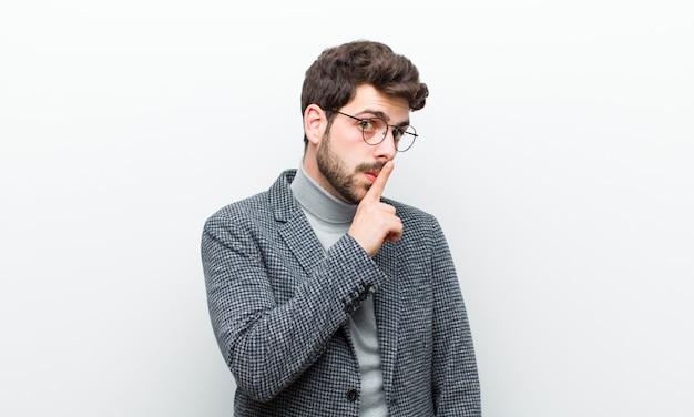Jonge managersmens die om stilte en het stille gebaren vragen die voor vinger shh zeggen of een geheim houden