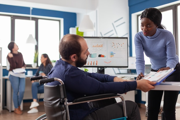 Jonge managervrouw die met financiële documenten werkt die grafieken controleert die met verlamde teamleider met een handicap praten