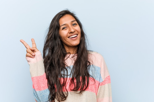Jonge manier indische vrouw blij en onbezorgd toont een vredessymbool met vingers.
