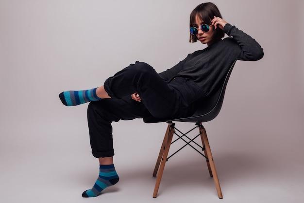 Jonge manier mooie vrouw die in zonnebril op geïsoleerde stoel zit