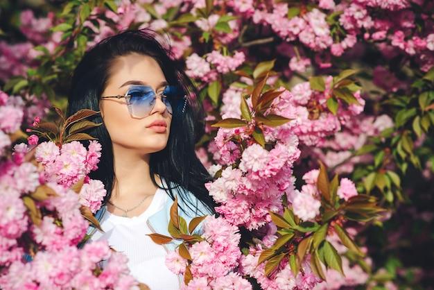 Jonge maniervrouw die door roze bloemen wordt omringd. lentedag. lente roze sakura bloesem. modieus meisje in trendy bril.