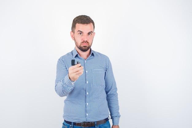 Jonge mannelijke aansteker in shirt, spijkerbroek houden en zelfverzekerd kijken. vooraanzicht.