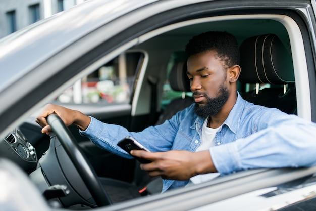 Jonge mannelijke afrikaanse amerikaan die zijn telefoon houdt terwijl zijn auto drijft
