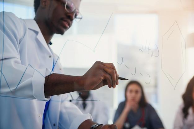 Jonge mannelijke afrikaanse arts trekt moleculaire formule op glas bord. een leraar in een laboratorium dat chemische formules schrijft op een transparant bord voor zijn leerling.
