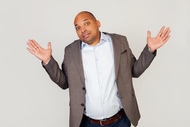 Jonge mannelijke afro-amerikaanse zakenman, haalt zijn schouders op, geen idee en verward uitdrukking met opgeheven armen
