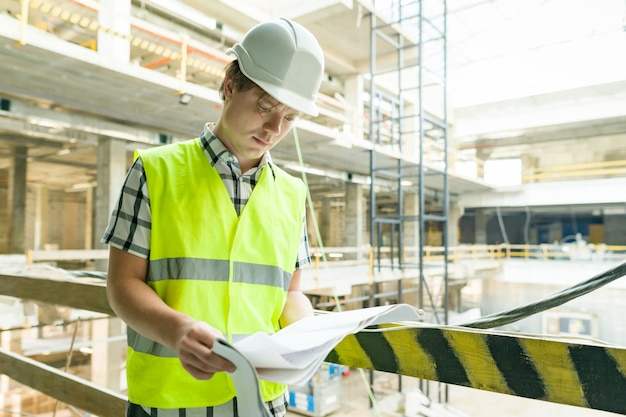 Jonge mannelijke architect bij een bouwwerf