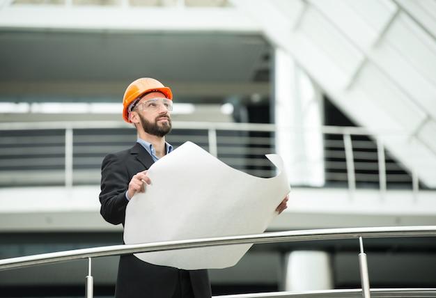 Jonge mannelijke architect in het moderne kantoor.