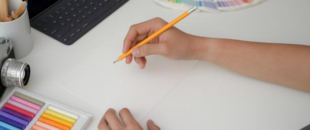 Jonge mannelijke artiest puttend uit papier schets