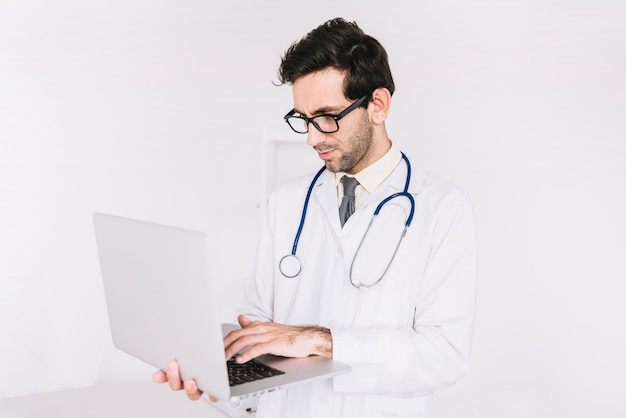 Jonge mannelijke arts die aan laptop werkt