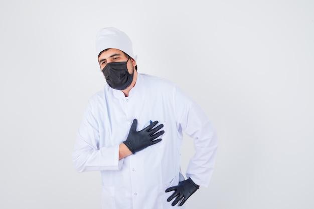 Jonge mannelijke arts die de hand op de borst houdt in een wit uniform en er uitgeput uitziet, vooraanzicht.
