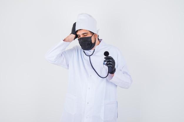 Jonge mannelijke arts die de hand op het hoofd houdt in wit uniform en er ziek uitziet, vooraanzicht.