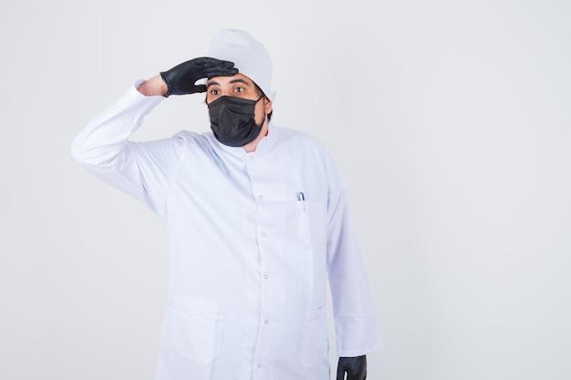 Jonge mannelijke arts die de hand op het voorhoofd houdt terwijl hij wegkijkt in een wit uniform en er gefocust uitziet. vooraanzicht.