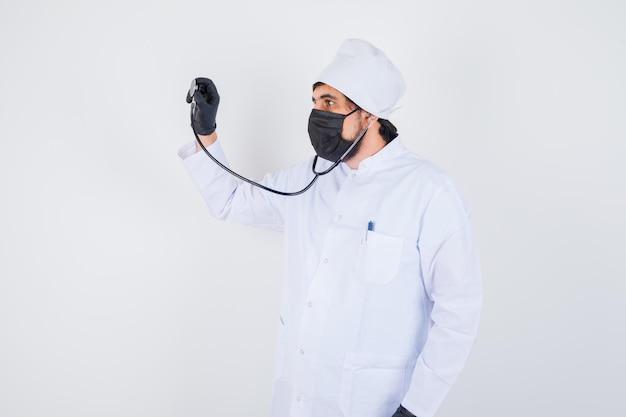 Jonge mannelijke arts die doet alsof hij de beats in wit uniform controleert en er zelfverzekerd uitziet, vooraanzicht.
