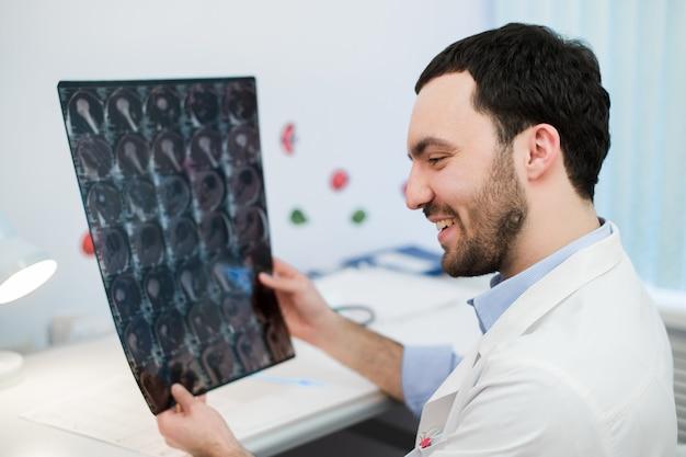 Jonge mannelijke arts die een mri-hersenscan leest en herziet