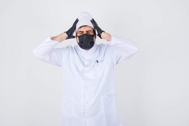 Jonge mannelijke arts die handen op een agressieve manier opheft in wit uniform en er geïrriteerd uitziet, vooraanzicht.