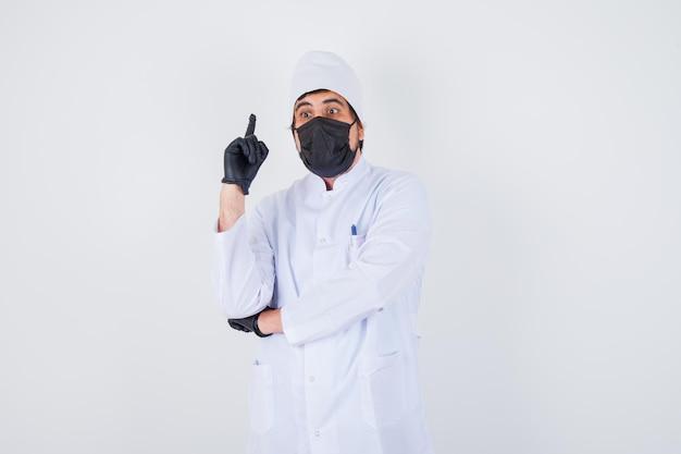 Jonge mannelijke arts die in wit uniform omhoog wijst en er zelfverzekerd uitziet, vooraanzicht.
