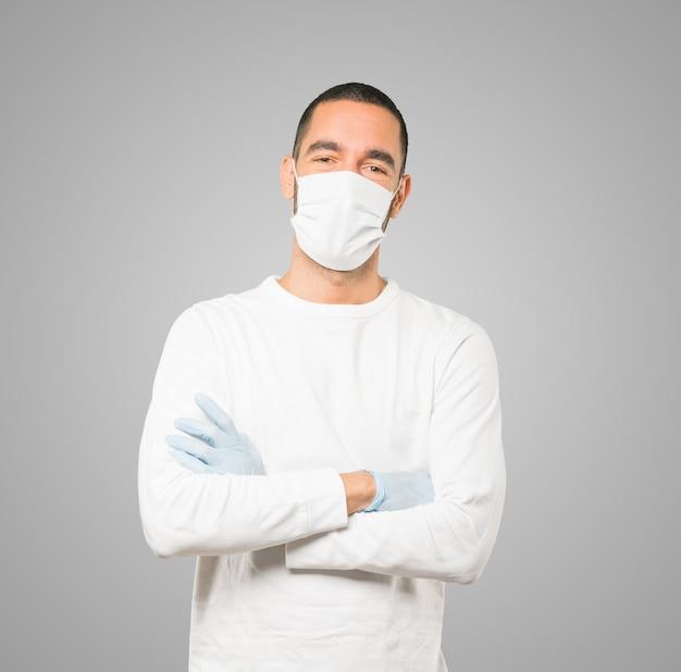 Jonge mannelijke arts die masker en beschermende handschoenen draagt
