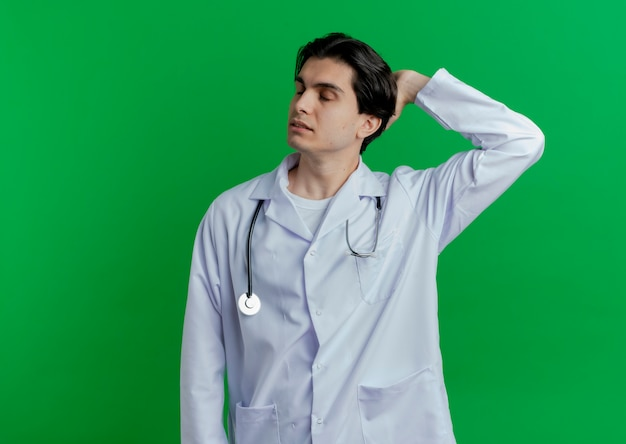 Jonge mannelijke arts die medische mantel en stethoscoop draagt die hand achter hoofd met gesloten geïsoleerde ogen houdt