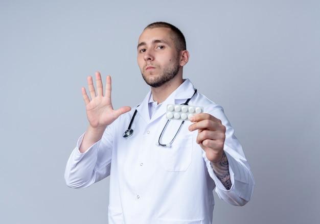 Jonge mannelijke arts die medische mantel en stethoscoop om zijn nek draagt ?? die pakje medische tabletten en vijf met hand toont en camera bekijkt die op witte achtergrond wordt geïsoleerd