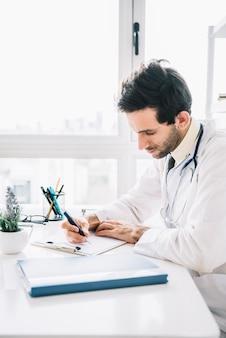 Jonge mannelijke arts die op klembord in kliniek schrijft