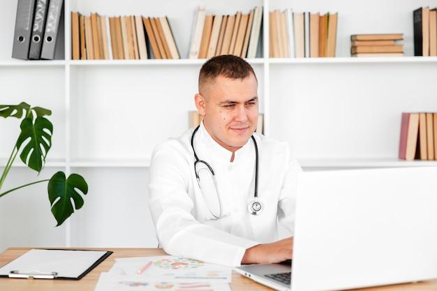 Jonge mannelijke arts die op laptop kijkt