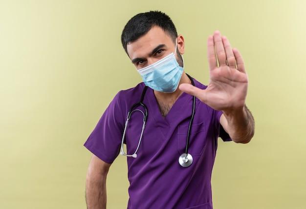 Jonge mannelijke arts die paarse chirurgenkleding en een stethoscoop medisch masker draagt dat stopgebaar op geïsoleerde groene muur toont