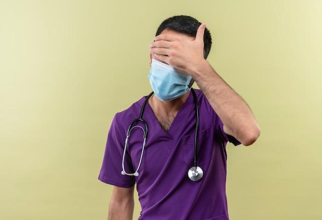 Jonge mannelijke arts die paarse chirurgenkleding en een stethoscoop medisch masker draagt en bedekte ogen met hand op geïsoleerde groene muur
