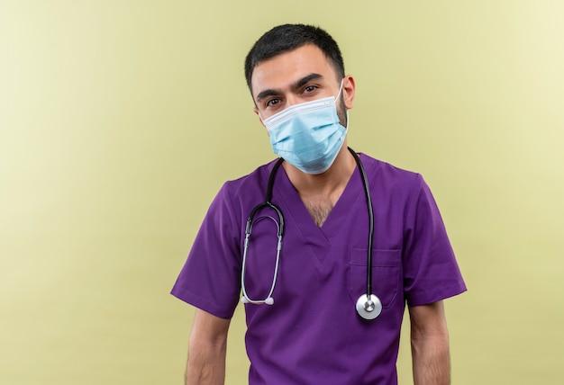 Jonge mannelijke arts die paarse chirurgenkleding en een stethoscoop medisch masker draagt op geïsoleerde groene muur