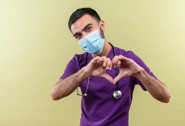 Jonge mannelijke arts die paarse chirurgenkleding en stethoscoop medisch masker draagt dat hartgebaar op geïsoleerde groene muur toont