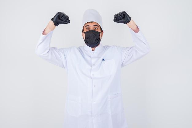 Jonge mannelijke arts die winnaargebaar in wit uniform toont en er gelukkig uitziet, vooraanzicht.