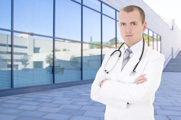 Jonge mannelijke arts die zich op straat tegen modern ziekenhuisgebouw bevindt
