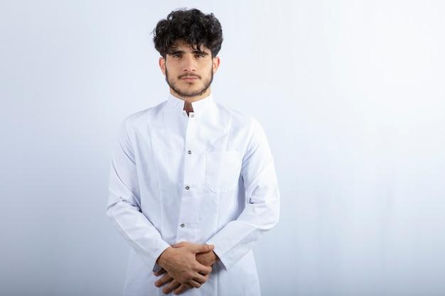 Jonge mannelijke arts die zich op witte muur bevindt.