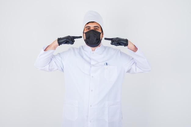 Jonge mannelijke arts die zichzelf in een wit uniform wijst en er trots uitziet, vooraanzicht.