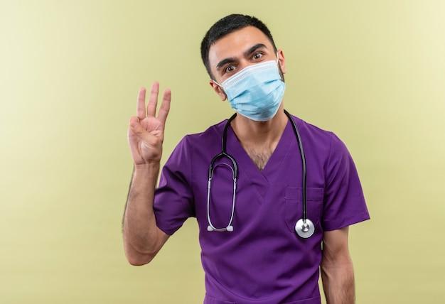 Jonge mannelijke arts draagt paarse chirurg kleding en stethoscoop medisch masker met drie op geïsoleerde groene muur