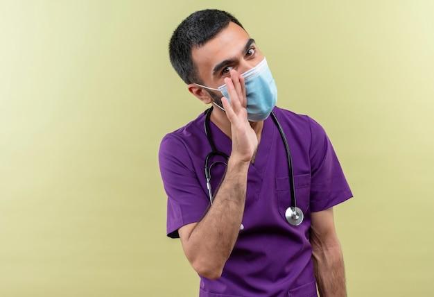 Jonge mannelijke arts draagt paarse chirurg kleding en stethoscoop medisch masker met gefluister gebaar op geïsoleerde groene muur