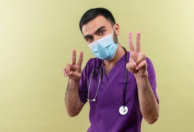 Jonge mannelijke arts draagt paarse chirurg kleding en stethoscoop medisch masker met vredesgebaar met beide handen op geïsoleerde groene muur